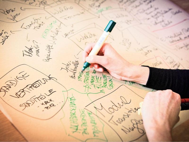 Bei einem Organisationstreffen der Agora Köln werden Ideen am Flipchart notiert.